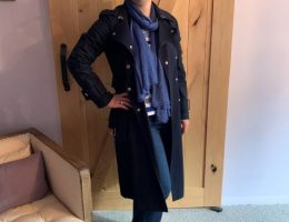 Lani Inlander of Real Life Style wearing a navy trench, blue scarf, jeans and boots